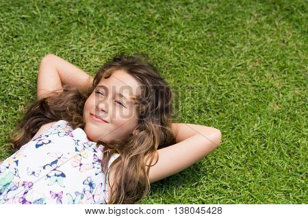 Beautiful little girl lying on green grass and looking up. Girl lost in her thoughts cheerfully smiling. Close up face of happy child thinking outdoor.