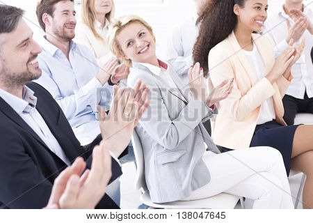 Happy young people applauding for a boss during official meeting in a company