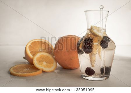 Fizzy lemonade with oranges and cherries in transparent glass jug on the white background