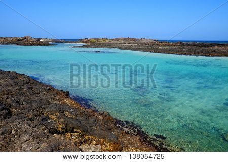 View on a lagoon with transparent blue water and on the volcanic cliffs on the island Lobos Spain.