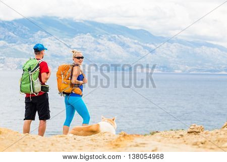 Happy couple hikers trekking with akita dog in summer mountains camping at seaside. Young woman and man walking on rocky mountain trail path looking at beautiful inspirational landscape view.