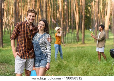 Joyful loving couple is relaxing in nature. They are standing and embracing. Man and woman are looking at camera and smiling. Their friends are playing badminton on background