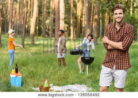 Attractive young man is making picnic with his friends in forest. He is standing and smiling. Couple is playing badminton. Woman is cooking food in grill on background