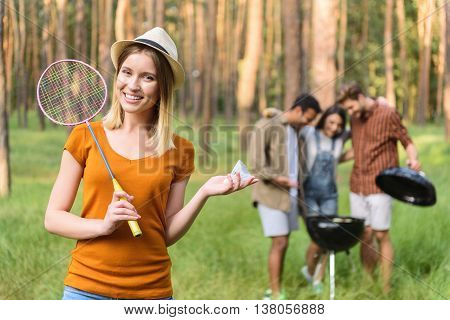 Lets play badminton. Pretty young woman is holding racket and shuttlecock. She is looking at camera playfully and smiling. Her friends are standing near grill in forest on background