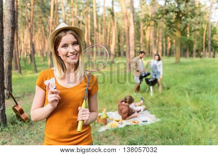Playful young girl is standing in forest with shuttlecock and racket. She is looking forward with invitation and laughing. Couple is cooking food on grill. Man is lying on blanket on background