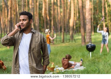 Young man is talking on phone with seriousness. Two girls are standing and playing badminton on background. Guy is lying on blanket in forest