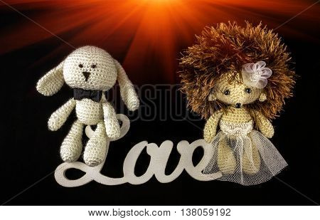 toy braided newlyweds the bride and groom on a black background. wedding symbols with the word love.