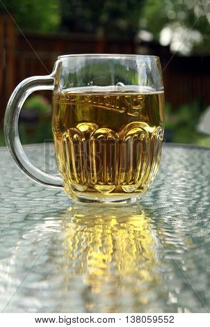A beer mug with amber beer on a glass table