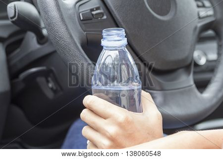 In the hands of a girl in a car with a bottle of fresh drinking water.