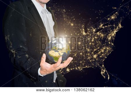 Business man holding the small world in his hands against america city night light.Save our planet earth ecology concept. (Elements of this image furnished by NASA)