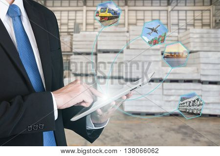 Logistic concept with businessman hand holding digital tablet shipping icons use for import export and logistic background.