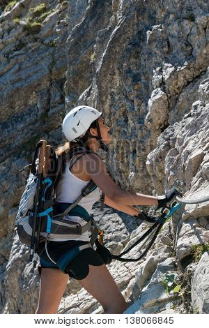 Single young woman in white helmet, backpack and climbing gear, climbing side of mountain at daytime