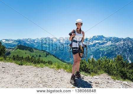Single pretty young woman in hiking outfit exploring in the mountains under clear sky