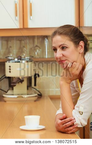 Pensive mature woman with cup of coffee in kitchen. Housewife female with hot energizing beverage. Caffeine energy.