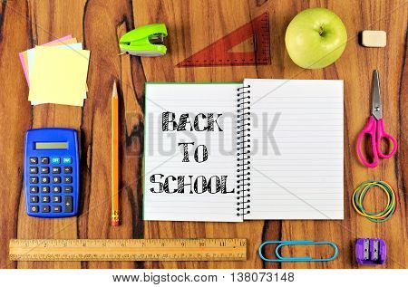 Opened School Notebook With Arrangement Of School Supplies And Back To School Text Over A Wooden Des