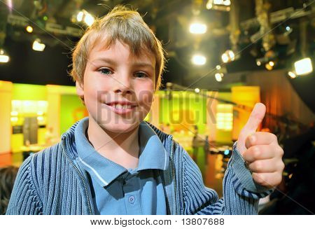 "Little smiling boy stands in auditorium and shows ""ok"" against the background of television broadcast"