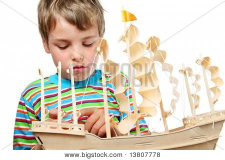 Small boy in striped shirt work with zeal on artificial ship, he fixes sails