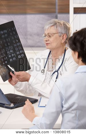 Doctor explaining patient scan results in bright office.?