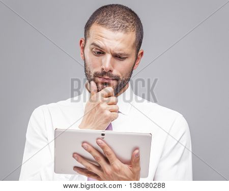 Thoughtful business man looking to his tablet computer on grey background