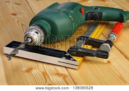 Electric drill and joinery tools on a wooden floor closeup