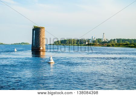 Summer panoramic view of architecture ensemble of Yuriev monastery and remnants of stone supports of unfinished bridge across the Volkhov river in Veliky Novgorod Russia. Summer architecture view