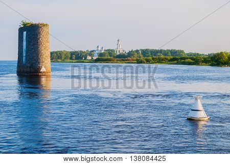 Summer panorama -architecture ensemble of Yuriev monastery and stone supports of unfinished bridge across the Volkhov river in Veliky Novgorod Russia. Sunset summer view. Soft filter applied