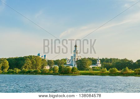 Summer panoramic landscape - architecture ensemble of Yuriev Orthodox male monastery on the bank of Volkhov river in Veliky Novgorod Russia sunset summer architecture view of Orthodox landmark