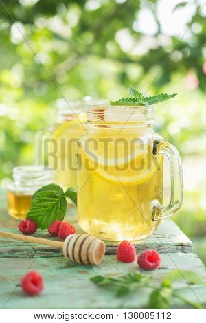 Iced tea with lemon slices and raspberry. A refreshing drink on a hot summer day in the garden. Shallow depth of field