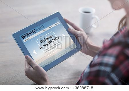 Composite image of build website interface against woman using tablet on a table
