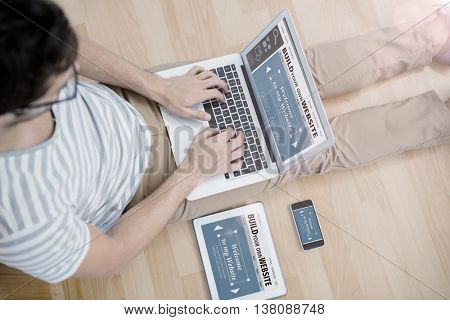 Composite image of build website interface against overhead view of a man using laptop in living room