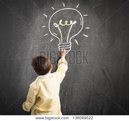 Child draws with chalk on the blackboard a light bulb
