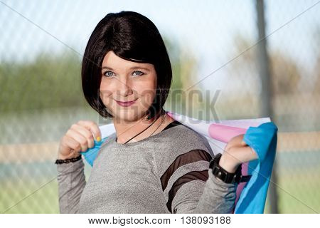 Short black haired Transgender girl holding pride flag over her shoulders.