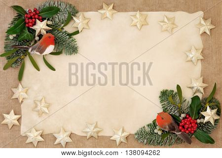 Christmas decorative background border with gold star and robin decorations, holly, ivy, mistletoe, snow covered  fir over old parchment and hemp paper.