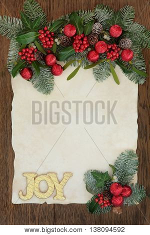 Christmas abstract background border with gold glitter joy sign, holly, ivy, mistletoe and snow covered fir on parchment paper over oak.