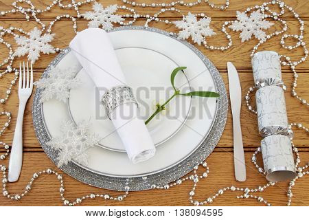 Sparkling christmas dinner table setting with white porcelain plates, cutlery, serviette and ring, mistletoe, silver bauble snowflake and bead decorations with cracker over oak background.