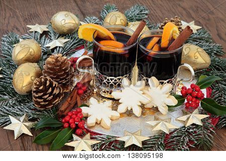 Christmas food and drink with mulled wine, gingerbread biscuits, with gold bauble decorations, spices, fruit, holly and snow covered fir over oak background.