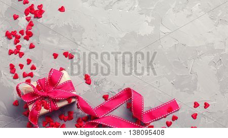 Festive gift box and many little decorative red hearts on textured grey background. Flat lay with copy space. Toned image.