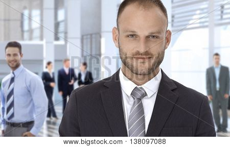 Smiling confident bristly caucasian businessman at business office center lobby, looking at camera.