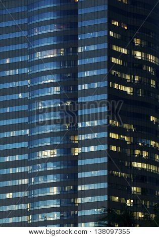 Windows Of Office Buildings Illuminated At Night For Background