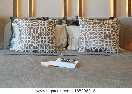 Stylish Bedroom Interior Design With Brown Pillows And Books On Bed.