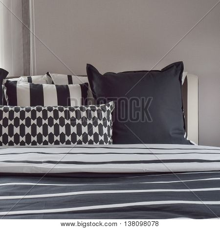 Modern Bedroom Interior With Pillows And Reading Lamp On Bedside Table