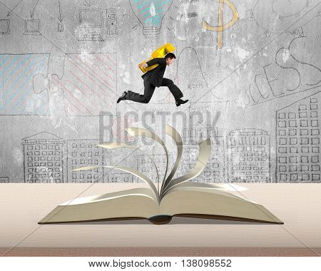 Man Holding Usd Money Sign Jumping On Top Of Flipping Pages Of Open Book On Table In Office With Doo