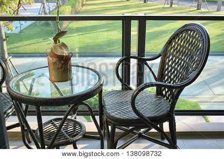 Brown Rattan Chair On Modern Balcony Overlooking A Garden