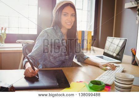 Female graphic designer using graphic tablet while working on computer at office