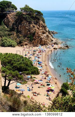 Sant Pol de Mar, Spain - July 9, 2016: People sunbathing on a beach located in a bay between Sant Pol de Mar and Clella in Costa Brava