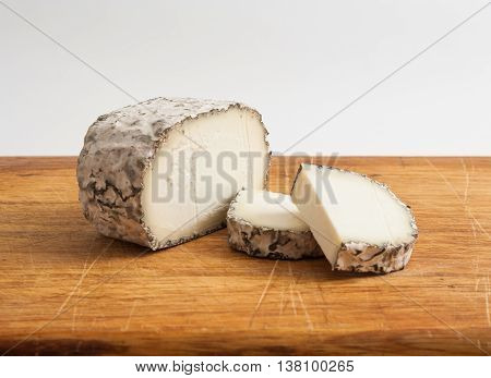 Artisanal goat cheese with mould on wooden cutting board.