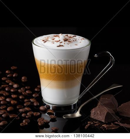 Frothy, layered cappuccino in a clear glass mug with cocoa sprinkled on top