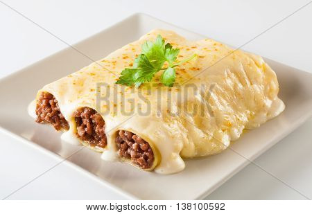 Delicious meat filled pasta on a plate. Italian cannelloni Spanish canelones.