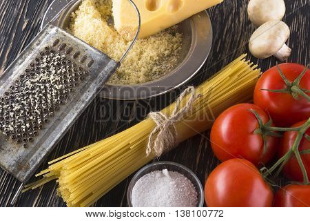 Penne pasta, garlic, tomatoes, cheese and a cutting board on a wooden surface.