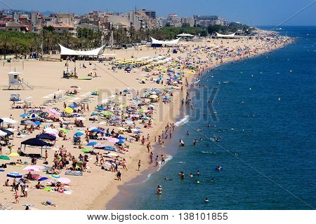 Calella, Spain - July 9, 2016: Aerial view of the beach of the crowded beach of Calella. This destination in Costa Brava is known for its cheap mass tourism